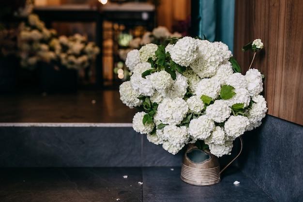 Wiaderko z kwiatami hortensji w kwiaciarni