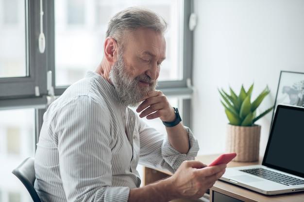 Wiadomość. mężczyzna w białej koszulce ze smartfonem w rękach pracuje w domu