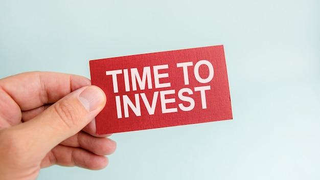 Wiadomość na czerwonej kartce czas inwestować, w rękach biznesmena. koncepcja finansów.
