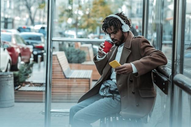 Wiadomość o przychodach. przystojny międzynarodowy mężczyzna pochyla głowę podczas czytania wiadomości