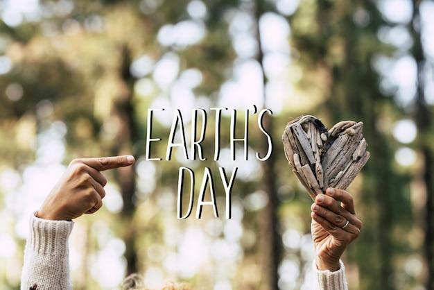 Wiadomość tekstowa na dzień ziemi z ludzkimi rękami biorącymi drewniane palenisko i zielone piękne nieostre drewniane sosny