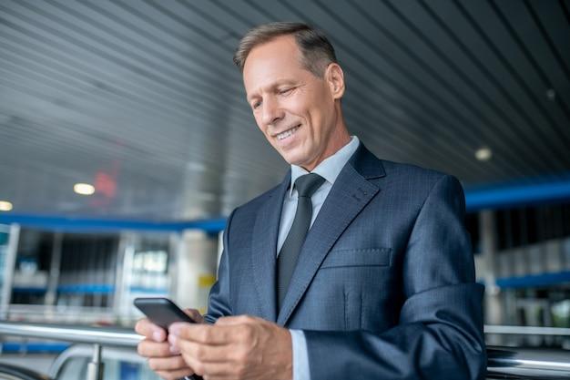 Wiadomość. uśmiechnięty biznesmen dorosły w ciemnym garniturze i krawacie, patrząc na smartfona z zainteresowaniem, stojąc w poczekalni na lotnisku