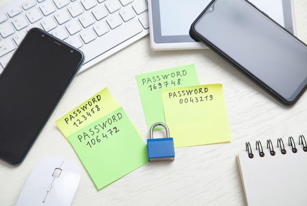 Wiadomość z hasłem napisana na karteczkach. smartfony, kłódka na biurku. bezpieczeństwo hasłem