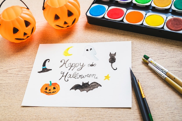 Wiadra i rzeczy do malowania w pobliżu rysunku halloween
