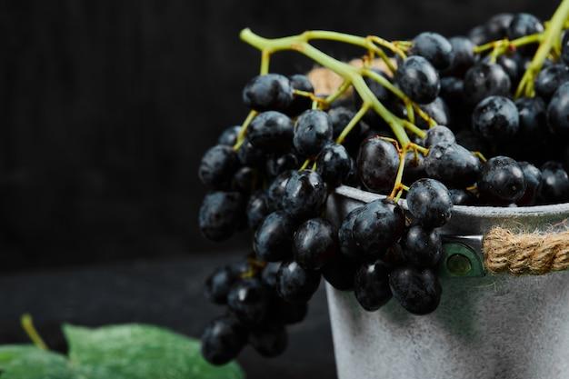 Wiadro czarnych winogron z liśćmi na ciemnym tle. wysokiej jakości zdjęcie