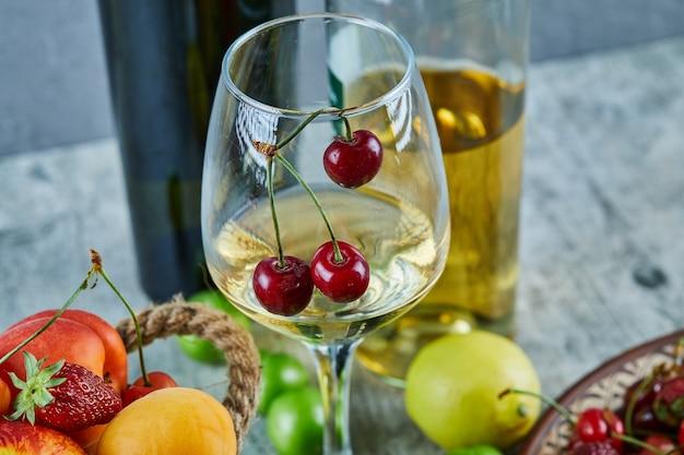 Wiadro letnich owoców, cytryny i kieliszek białego wina na marmurowej powierzchni