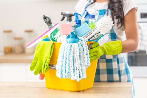 Wiadro pełne rzeczy do sprzątania domu na biurku w kuchni z kobietą trzymającą je w gumowych rękawiczkach.