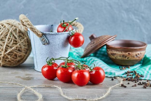 Wiadro pomidorów i goździków na drewnianym stole z pustą miską