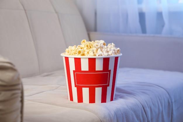 Wiadro popcornu na kanapie. oglądanie filmów w domu