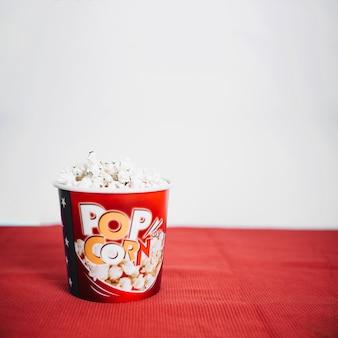 Wiadro pyszne popcorn na czerwonym suknem