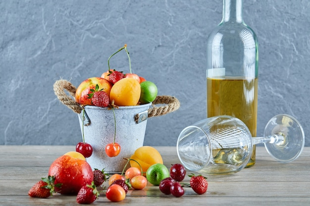 Wiadro świeżych owoców lata, butelka białego wina i pusty kieliszek na drewnianym stole.