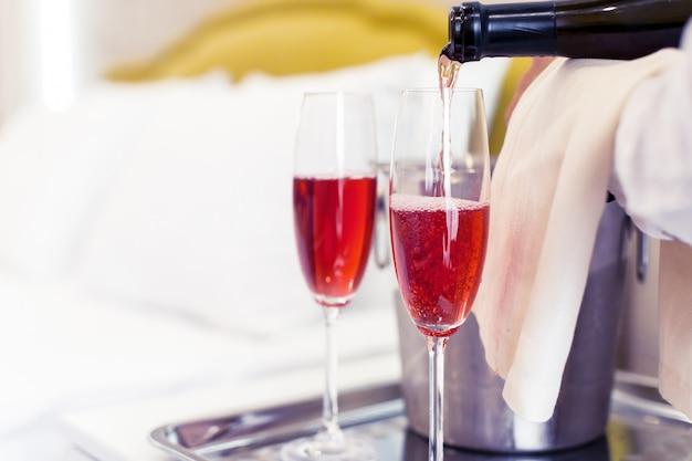Wiadro szampana w pobliżu łóżka w pokoju hotelowym