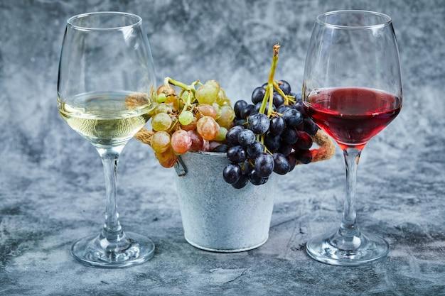 Wiadro winogron i szklanki wina na marmurze.