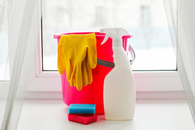 Wiadro z elementami czyszczącymi na białym oknie