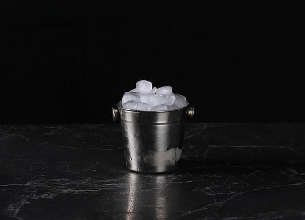 Wiadro z kostkami lodu do chłodzenia na czarnym tle