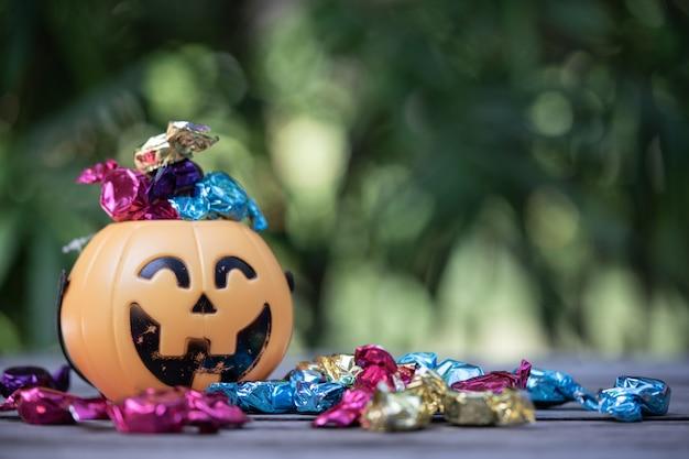 Wiadro z latarnią halloween z rozlanym cukierkiem