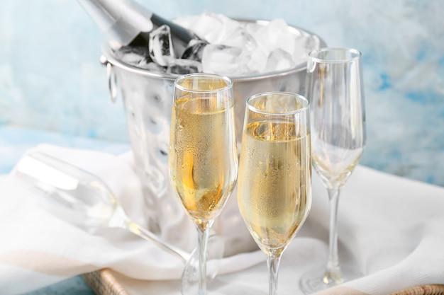 Wiadro z lodem i szampanem na kolorowym tle