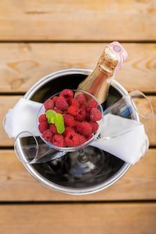 Wiadro z lodem, szampanem i świeżymi jagodami na drewnianym molo. ustaw na romantyczną randkę