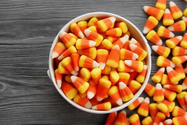 Wiadro z smacznymi halloweenowymi cukierkami na drewnianym stole
