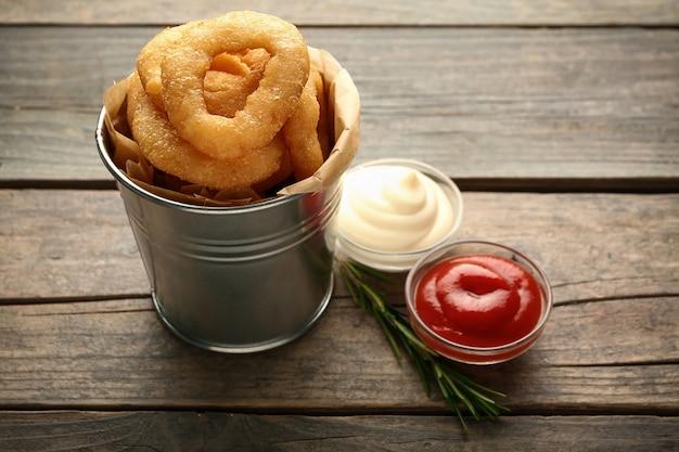 Wiadro z smacznymi krążkami cebulowymi i sosami na drewnianym stole