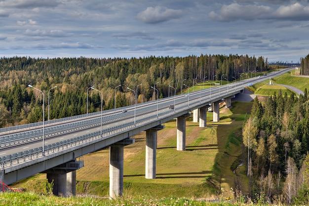 Wiadukt mostu stalowego na betonowych filarach, autostrada przecina las rosyjski.