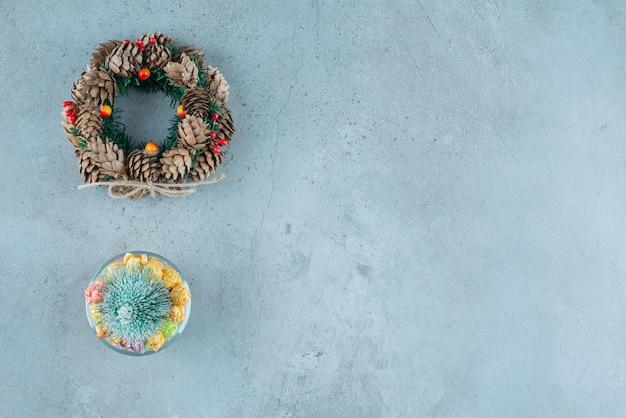 Wianek bożonarodzeniowy i pojemnik na cukierki z nogulami i figurką drzewka na marmurze.
