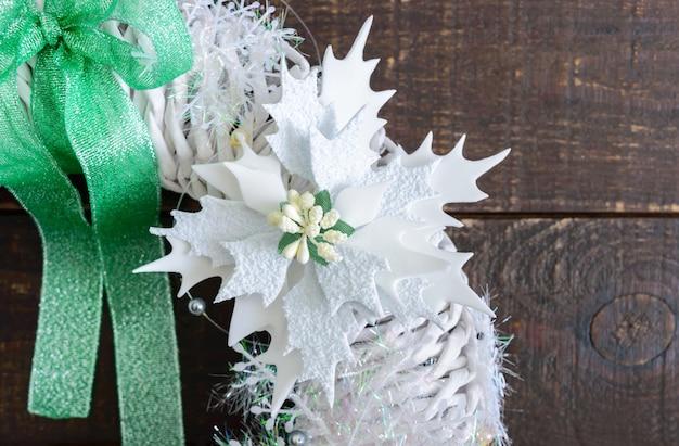 Wianek bożonarodzeniowy w kolorze białym ozdobiony świątecznymi dekoracjami na drewnianym tle. domowe rzemiosło świąteczne. niektóre elementy zbliżenia