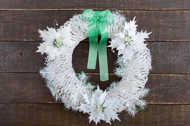 Wianek bożonarodzeniowy w kolorze białym ozdobiony świątecznymi dekoracjami na drewnianym tle. domowe rzemiosło świąteczne