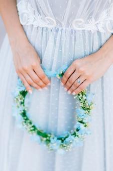 Wianek na głowie z niebiesko-białych kwiatów w dłoni panny młodej