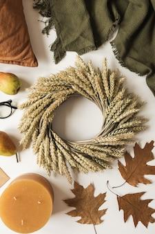 Wianek ze słomy pszenicznej, koc, poduszka, szklanki, gruszki, okrycie, suche jesienne liście i świeca na białym tle