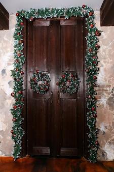 Wianki i ozdoby świąteczne na drzwiach domu.