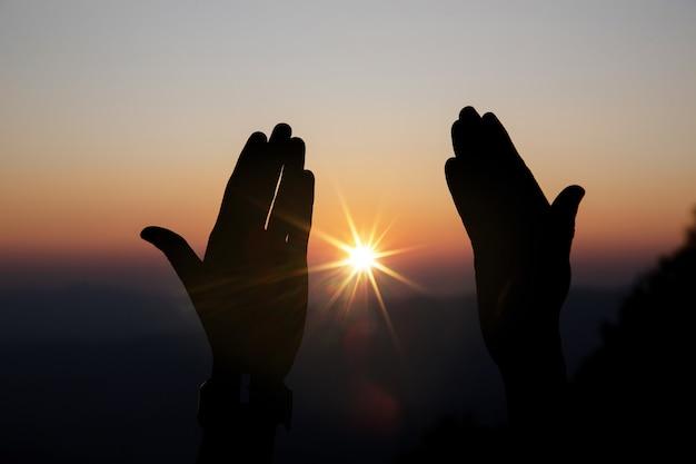 Wiara chrześcijańskiej koncepcji: duchowe ręce modlitwy nad słońcem świecą