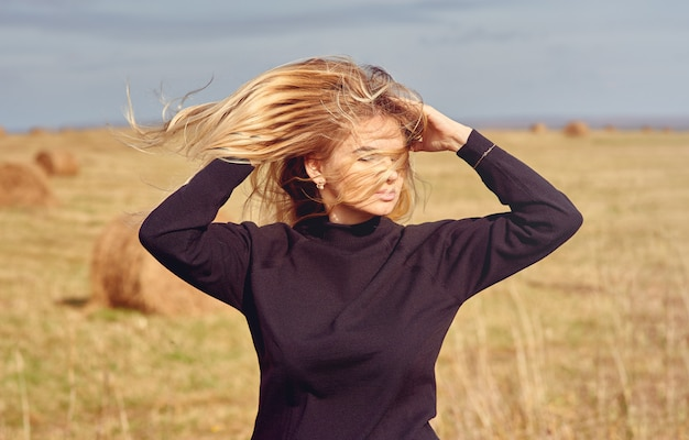 Wiatr wiejący długie włosy młodej dziewczyny na zewnątrz
