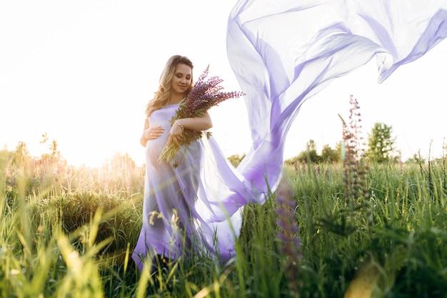 Wiatr wieje w fioletową sukienkę kobiety w ciąży, podczas gdy ona stoi w polu lawendy
