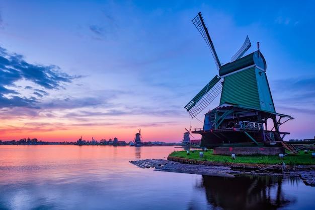Wiatraki w słynnym miejscu turystycznym zaanse schans w holandii z dramatycznym niebem. zaandam, holandia