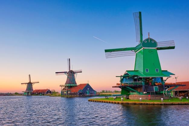 Wiatraki w zaanse schans w holandii na zachodzie słońca. zaandam, holandia