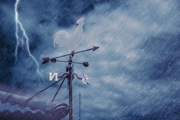 Wiatrowskaz na dachu domu na tle burzy pada wietrznie czarne pochmurne ciemne niebo z piorunem lub uderzeniem pioruna