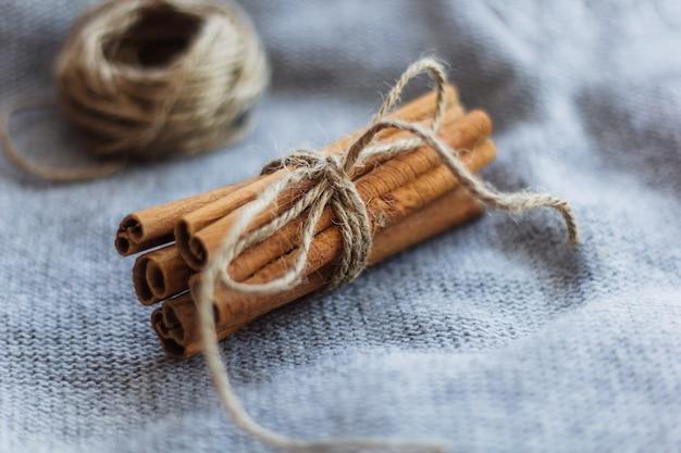 Wiązane suszone laski cynamonu na szarym tle z dzianiny