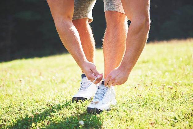 Wiązanie butów sportowych. młody sportowiec przygotowuje się do treningu sportowego i fitness na świeżym powietrzu.