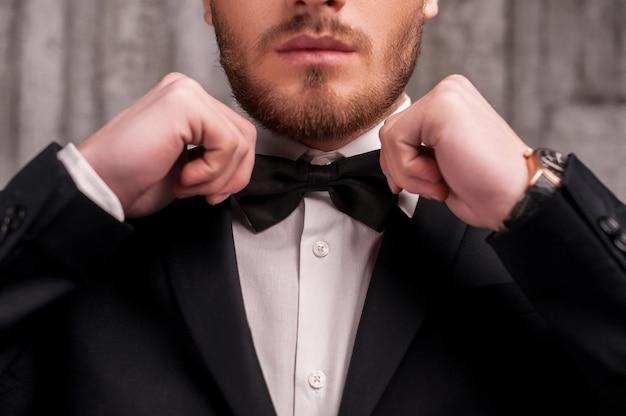 Wiązanie muszki. przycięty obraz przystojnego młodego mężczyzny z brodą w formalnej odzieży dopasowującej muszkę