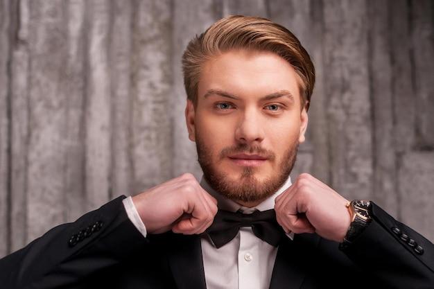 Wiązanie muszki. przystojny młody mężczyzna w formalnej odzieży poprawia muszkę i patrzy na kamerę