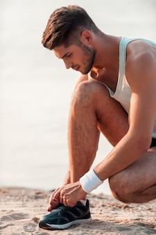 Wiązanie sznurowadeł dla dobrego biegania. zbliżenie: mężczyzna wiązania sznurowadeł na butach sportowych siedząc na plaży