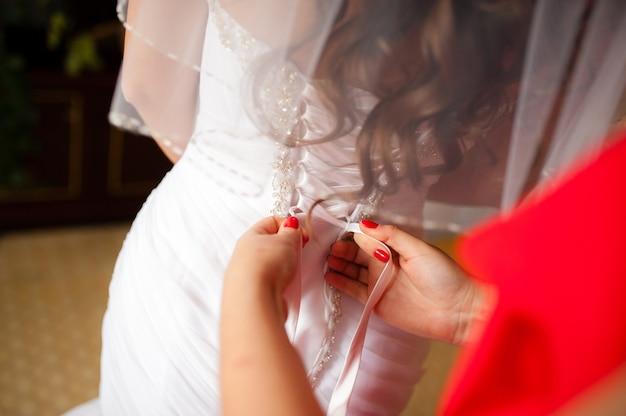 Wiązanie sznurowania na sukni ślubnej