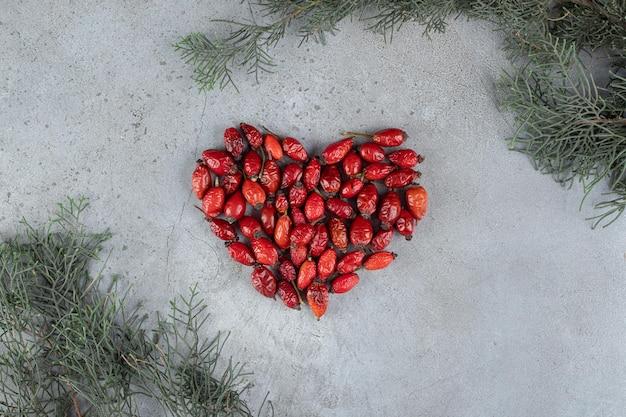 Wiązanka w kształcie serca z dzikiej róży i gałęzi na marmurowej powierzchni