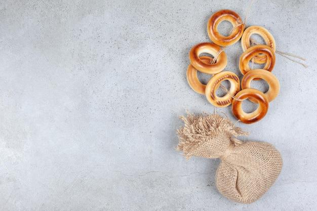 Wiązany pierścień sushki i worek na marmurowym tle.