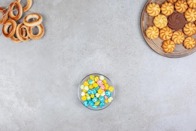 Wiązany pierścień sushki, mała miseczka cukierków popcornowych i taca ciastek na marmurowym tle. wysokiej jakości zdjęcie