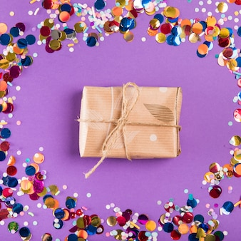 Wiązany sznurek nad owiniętą prezentem otoczony kolorowymi konfetti na fioletowym tle