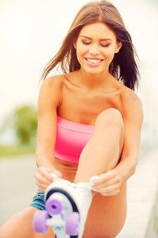 Wiąże jej wrotki. piękna młoda uśmiechnięta kobieta wiążąca wrotki siedząc na parapecie na zewnątrz