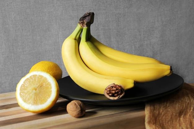 Wiązka bananów na czarnym talerzu z cytrynami i orzechami