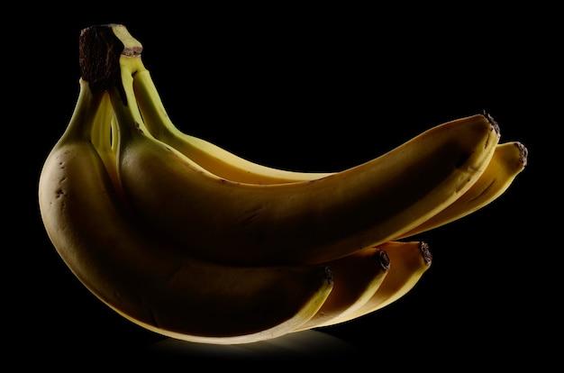 Wiązka bananów na czarnym tle. technika low-key
